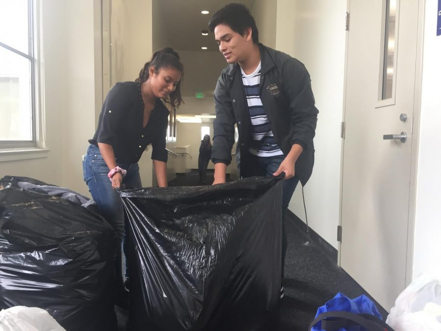 Ashley Flores and Cromwell Anaya, from left to right, collect clothing from bins in the English classrooms. As the Clothing Drive boxes filled up, they gathered the contents to make room for more donations.