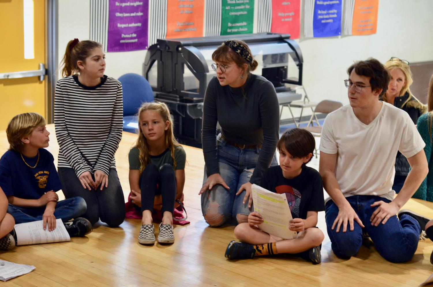 (Left to Right) juniors Kelsey Bailey, Chloe Bryan, and Will Purdy guide a group of elementary kids through their lines. The three, along with five others, extended a helping hand last Thursday with their production of