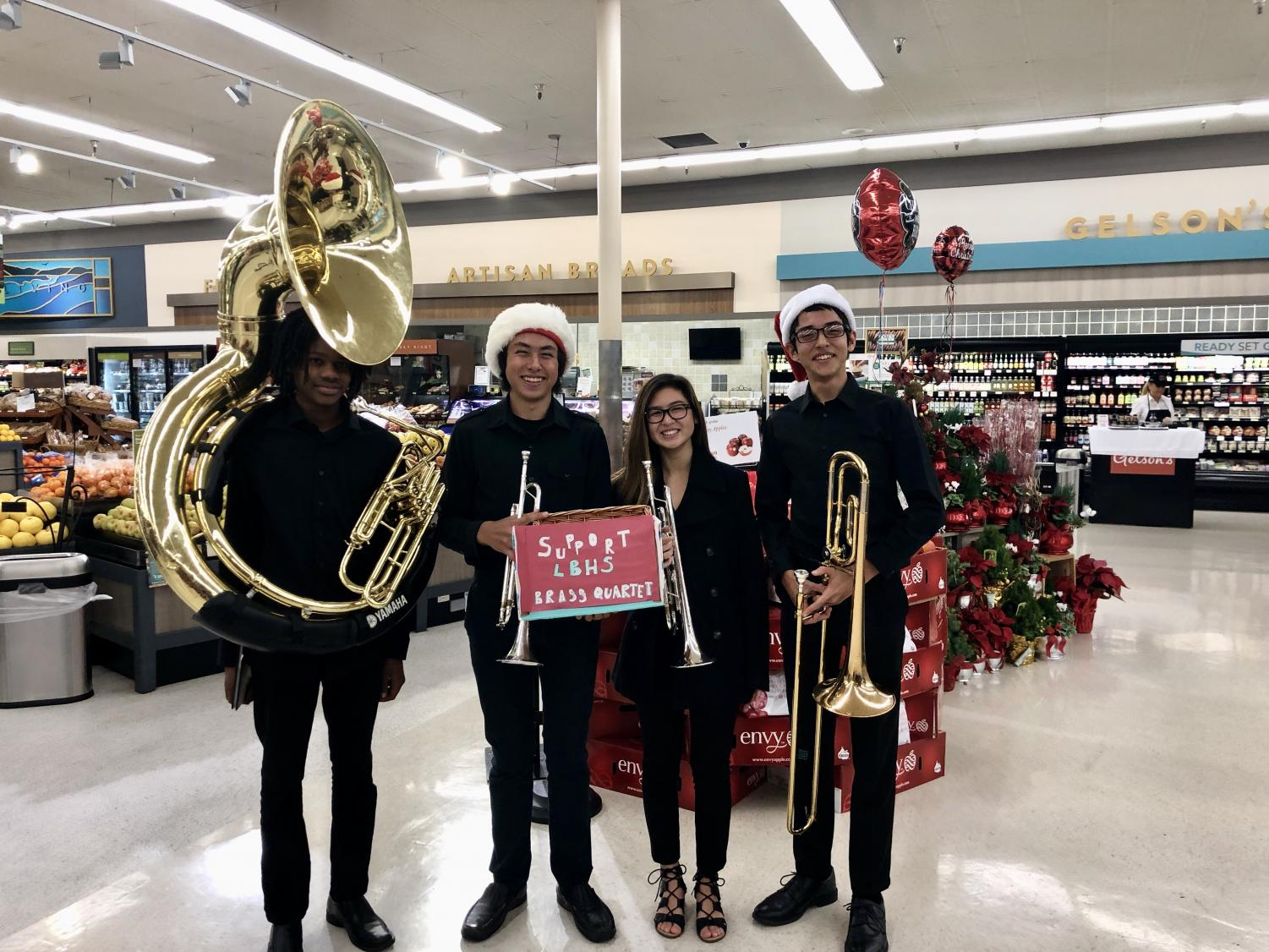 The brass quartet -  Zachary Duncan, sousaphone; Mason Lebby, trumpet; Jordan Sitea, trumpet; and Ryan Davison, trombone - takes a breather between songs at Gelson's Market. They have also performed at Hospitality Night, Trader Joe's, and the teachers' annual holiday breakfast.