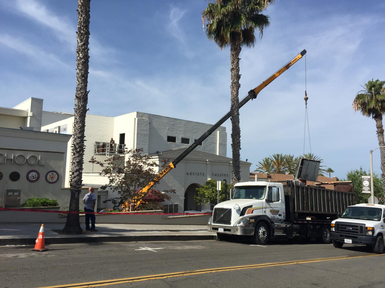 Construction crews use crane to place AC units on the theatre roof.