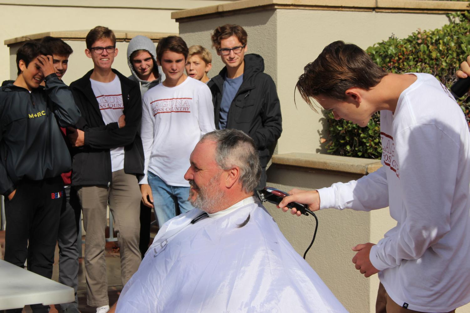 The varsity cross country team watches as Logan Brooks shaves Coach Wittkop's head in front of the whole school at lunch. In the beginning of the season, Wittkop promised his players that if they won CIF and state they could shave his head.