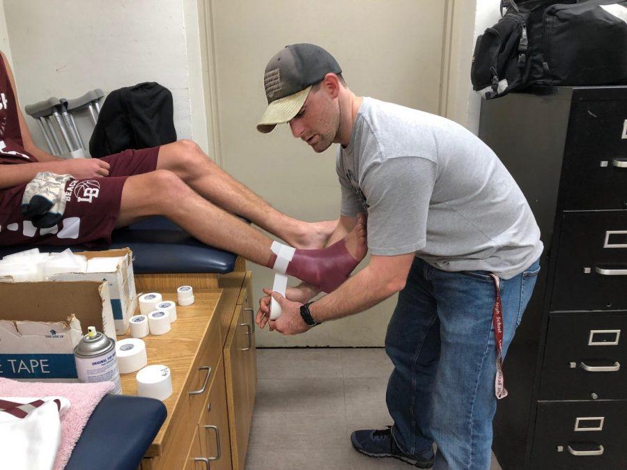 Tim+Crillly+helping+an+athlete.