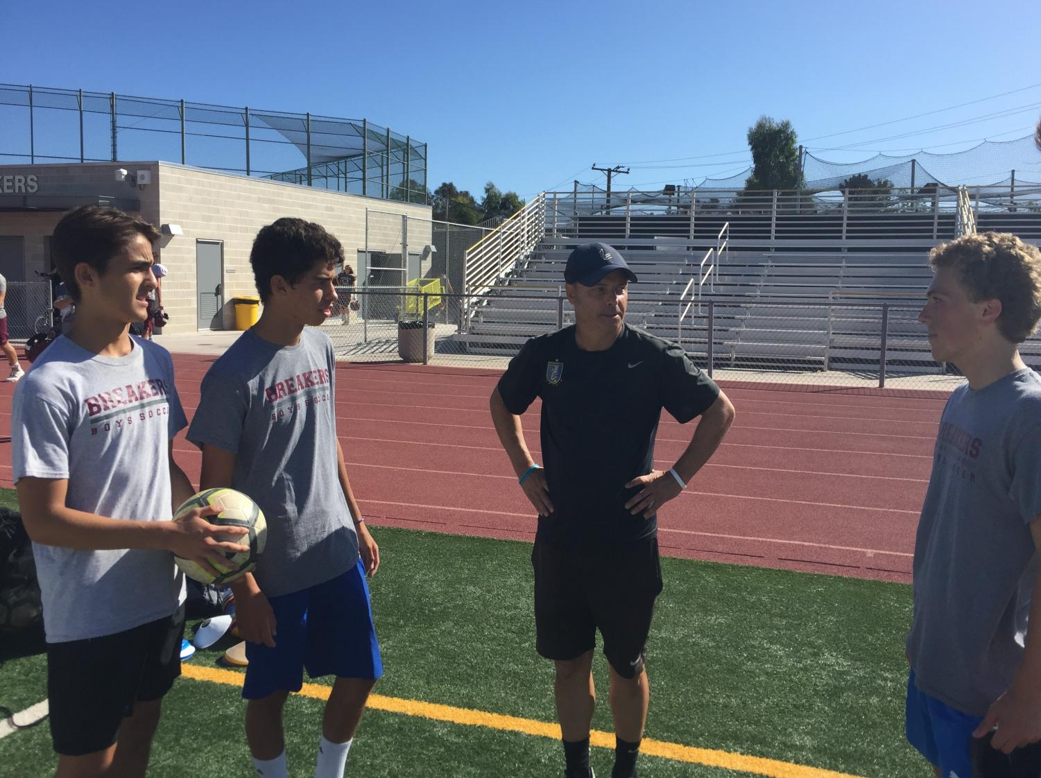 Thomas (center) talks to his players (from left to right) Adrian Ricci-Fisher, Diego Tellez Rodriquez and Griffin Kristensen about the upcoming season. Coach Thomas has found success with the team in the past and looks to continue that success with his new players.